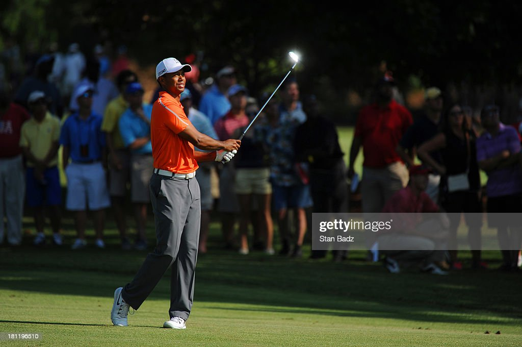<a gi-track='captionPersonalityLinkClicked' href=/galleries/search?phrase=Tiger+Woods&family=editorial&specificpeople=157537 ng-click='$event.stopPropagation()'>Tiger Woods</a> hits a shot to the 14th green during the first round of the TOUR Championship by Coca-Cola, the final event of the PGA TOUR Playoffs for the FedExCup, at East Lake Golf Club on September 19, 2013 in Atlanta, Georgia.