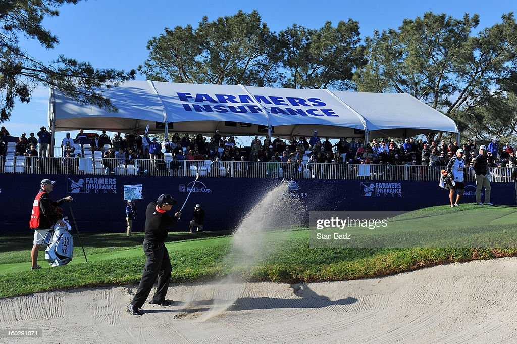 Tiger Woods hits from a bunker on the 17th hole during the final round of the Farmers Insurance Open at Torrey Pines Golf Course on January 28, 2013 in La Jolla, California.