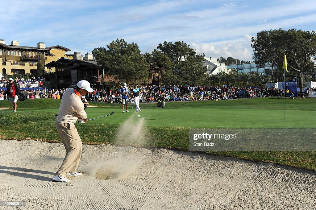 Tiger Woods hits from a bunker on the 18th hole during the first round of the Farmers Insurance Open at Torrey Pines Golf Course on January 24, 2013 in La Jolla, California.