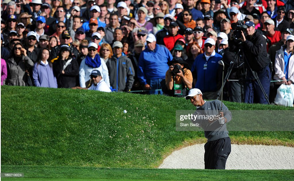 Tiger Woods hits from a bunker on the 18th hole during the third round of the Farmers Insurance Open at Torrey Pines Golf Course on January 27, 2013 in La Jolla, California.