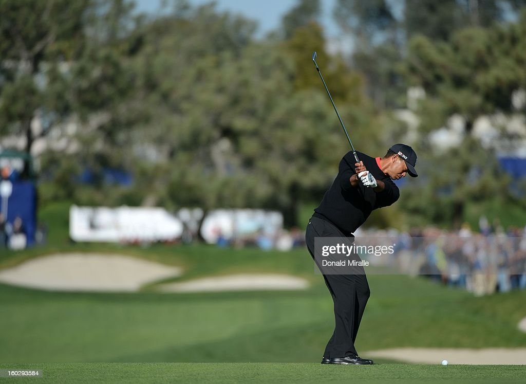 Tiger Woods hits his approach shot on the 17th hole en route to his -14 under victory during the Final Round at the Farmers Insurance Open at Torrey Pines Golf Course on January 28, 2013 in La Jolla, California.