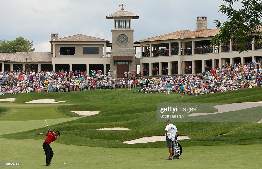 <a gi-track='captionPersonalityLinkClicked' href=/galleries/search?phrase=Tiger+Woods&family=editorial&specificpeople=157537 ng-click='$event.stopPropagation()'>Tiger Woods</a> hits his approach shot on the 18th hole as his caddie <a gi-track='captionPersonalityLinkClicked' href=/galleries/search?phrase=Joe+LaCava&family=editorial&specificpeople=695531 ng-click='$event.stopPropagation()'>Joe LaCava</a> looks on during the final round of the Memorial Tournament presented by Nationwide Insurance at Muirfield Village Golf Club on June 2, 2013 in Dublin, Ohio.