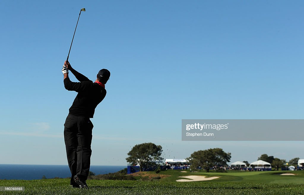 Tiger Woods hits his second shot on the 14th hole during the final round of the Farmers Insurance Open on the South Course at Torrey Pines Golf Course on January 28, 2013 in La Jolla, California.