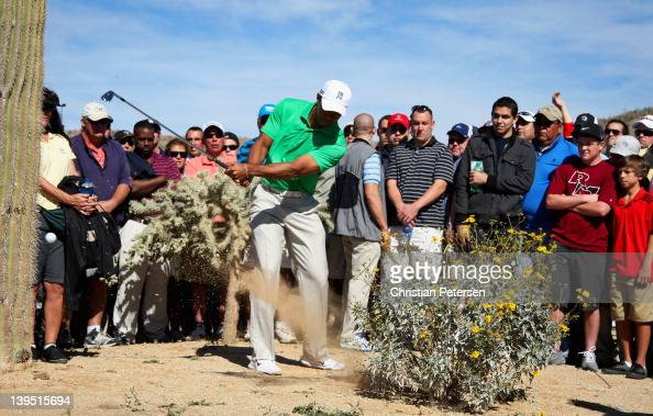 Tiger Woods hits lefthanded out of a waste area on the second hole as a gallery of fans look on during the first round of the World Golf...