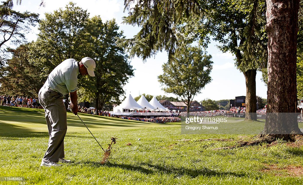 Tiger Woods hits out from under a tree in the rough on the 18th fairway during the Third Round of the World Golf Championships-Bridgestone Invitational at Firestone Country Club South Course on August 3, 2013 in Akron, Ohio.