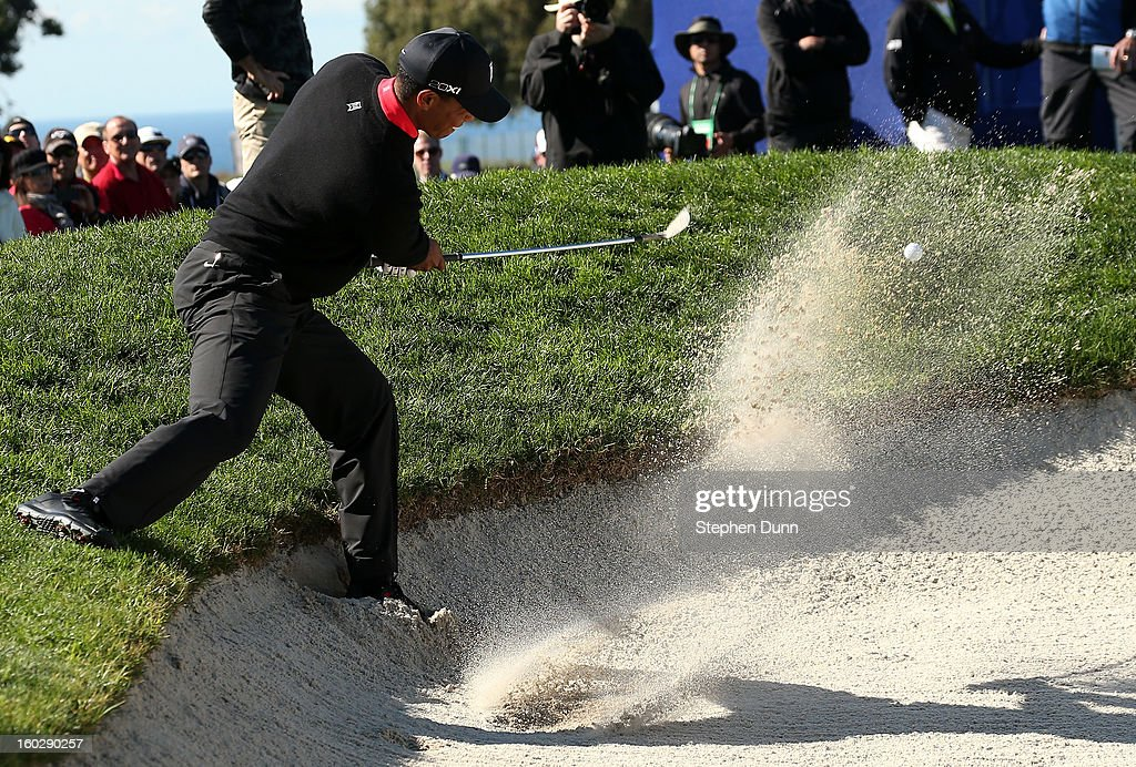 Tiger Woods hits out of a bunker on the 11th hole during the final round of the Farmers Insurance Open on the South Course at Torrey Pines Golf Course on January 28, 2013 in La Jolla, California.