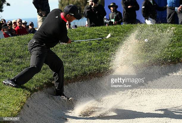 Tiger Woods hits out of a bunker on the 11th hole during the final round of the Farmers Insurance Open on the South Course at Torrey Pines Golf...