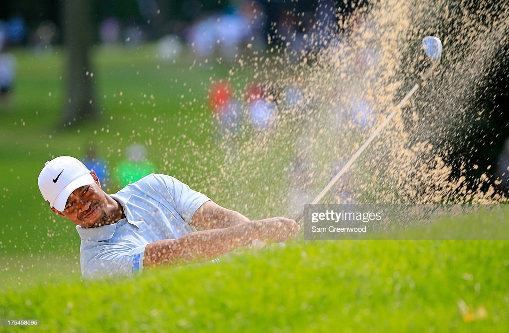 Tiger Woods hits out of a bunker on the ninth hole during the Third Round of the World Golf Championships-Bridgestone Invitational at Firestone Country Club South Course on August 3, 2013 in Akron, Ohio.