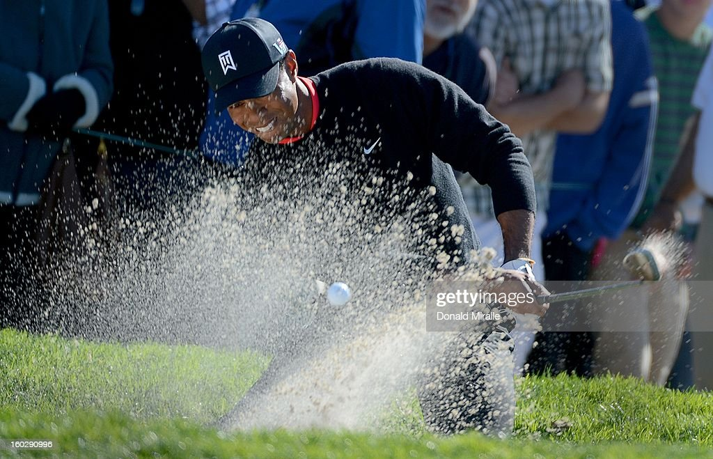 Tiger Woods hits out of the 11th green bunker en route to his -14 under victory during the Final Round at the Farmers Insurance Open at Torrey Pines Golf Course on January 28, 2013 in La Jolla, California.