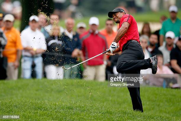 Tiger Woods hits out of the rough on the second hole during the final round of the World Golf ChampionshipsBridgestone Invitational at Firestone...