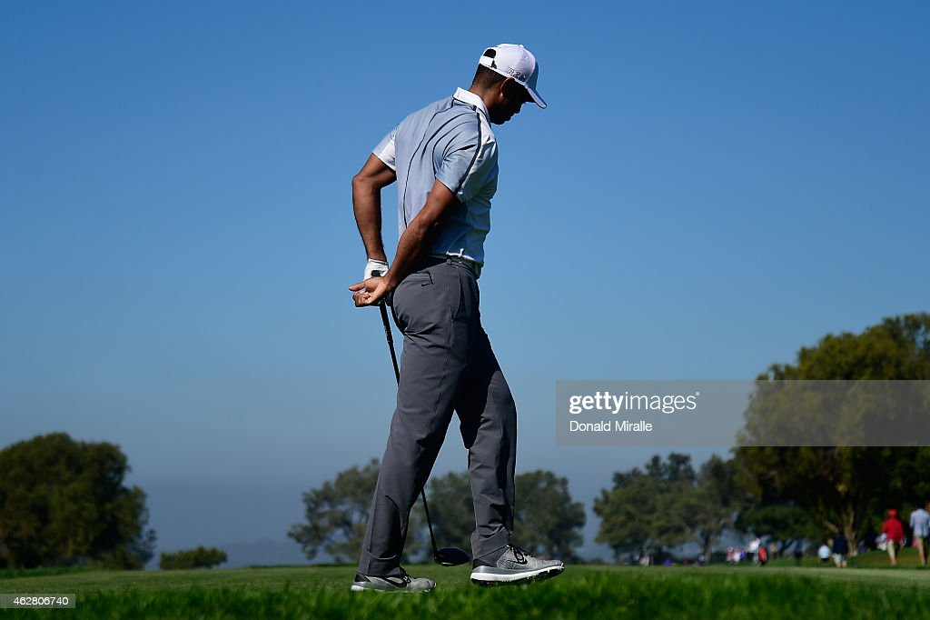Tiger Woods holds his back after playing his tee shot on the 15th hole of the north course during the first round of the Farmers Insurance Open at Torrey Pines Golf Course on February 5, 2015 in La Jolla, California.