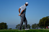 Tiger Woods holds his back after playing his tee shot on the 15th hole of the north course during the first round of the Farmers Insurance Open at...