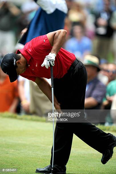 Tiger Woods holds his left leg in pain after teeing off on the second tee in the fourth round of the 108th US Open golf tournament at Torrey Pines...