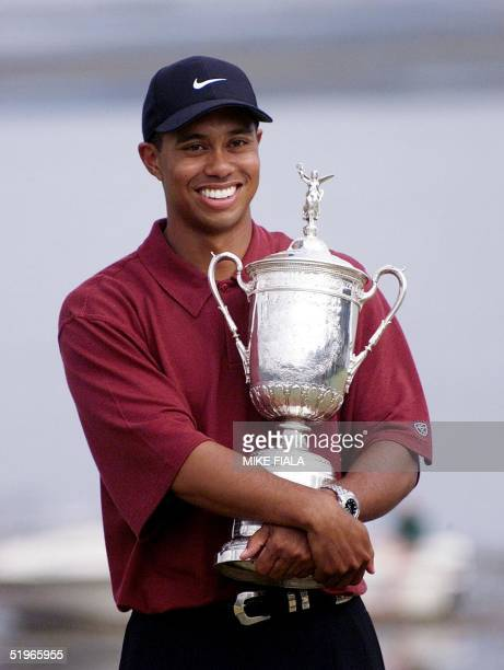 Tiger Woods hugs his US Open Trophy on the 18th Green after winning the tournament at Pebble Beach in California 18 June 2000 Woods won the...