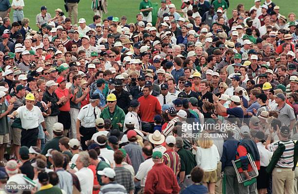 Tiger Woods is surrounded by a huge gallery of fans after hitting his approach shot to the 18th hole 13 April 1997 during the final round of the...