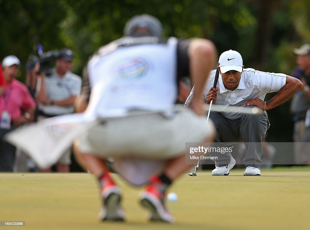 Tiger Woods lines up a putt with caddy Joe LaCava during the third round of the WGC-Cadillac Championship at the Trump Doral Golf Resort & Spa in on March 9, 2013 in Doral, Florida.