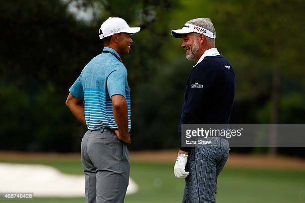 Tiger Woods of the United States and Darren Clarke of Northern Ireland talk on the practice range during a practice round prior to the start of the...