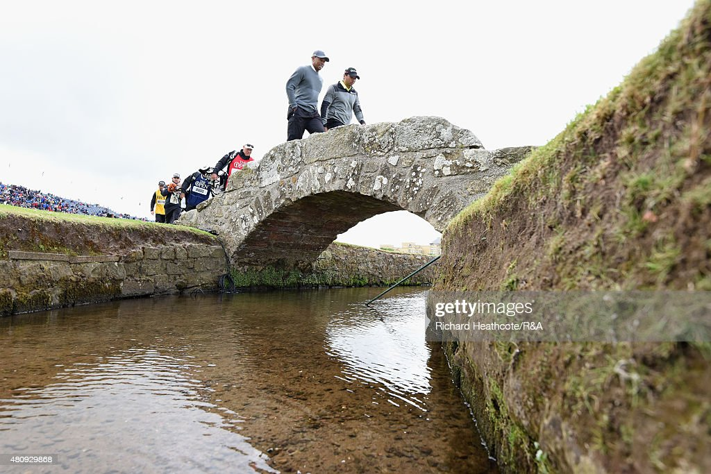 Tiger Woods of the United States and Jason Day of Australia walk over Swilcan Bridge with their caddies during the first round of the 144th Open Championship at The Old Course on July 16, 2015 in St Andrews, Scotland.