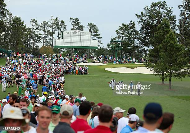 Tiger Woods of the United States and Mark O'Meara of the United States walk up a fairway with their caddies as a gallery of patrons look on during a...