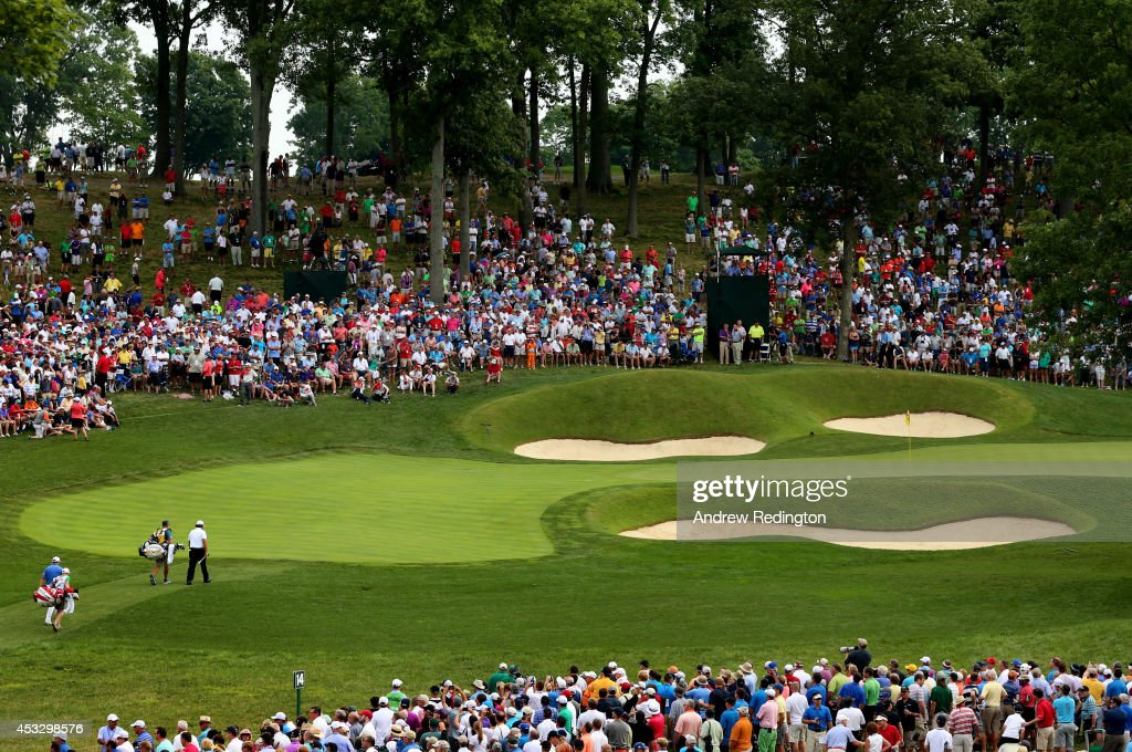 Tiger Woods of the United States and Padraig Harrington of Ireland walk onto the 14th green with their caddies during the first round of the 96th PGA Championship at Valhalla Golf Club on August 7, 2014 in Louisville, Kentucky.