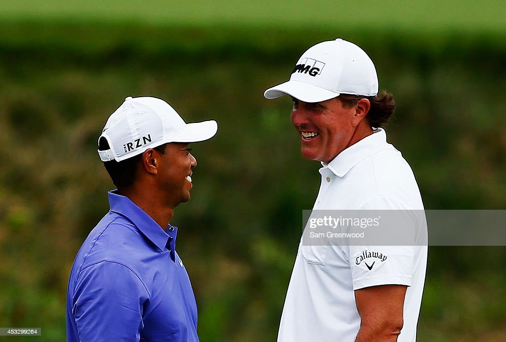 Tiger Woods of the United States and Phil Mickelson of the United States laugh together on the 16th green during the first round of the 96th PGA Championship at Valhalla Golf Club on August 7, 2014 in Louisville, Kentucky.