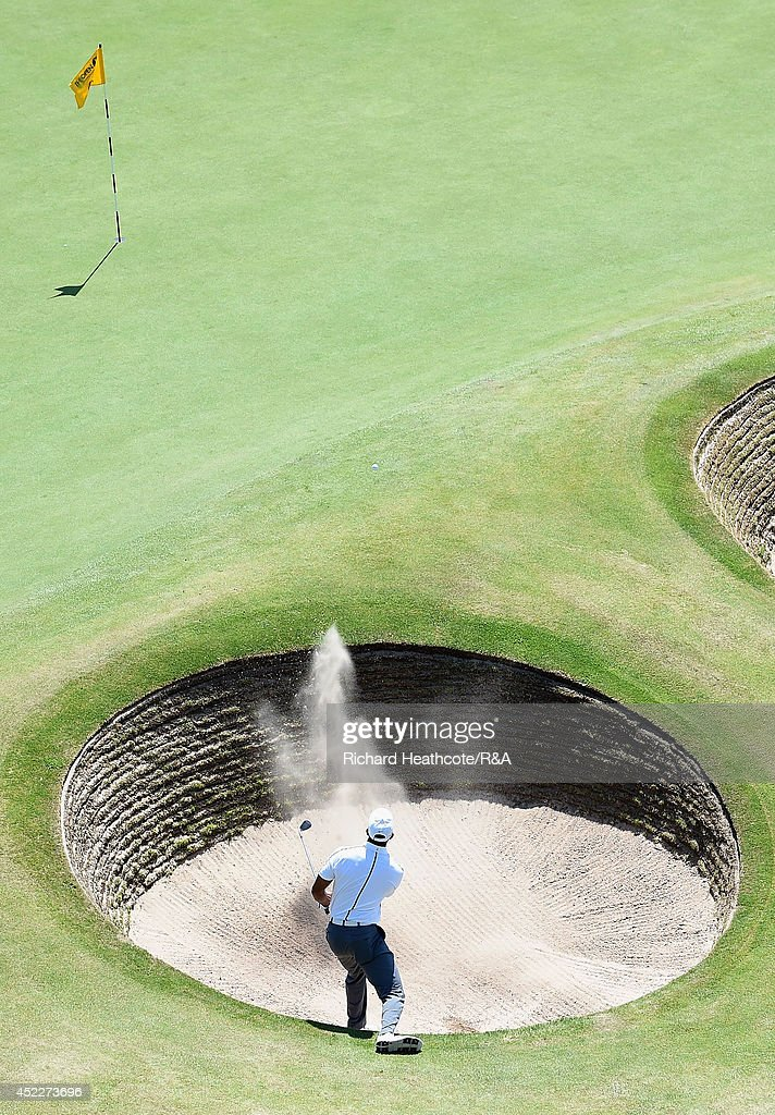 Tiger Woods of the United States chips from a bunker onto the 18th green during the first round of The 143rd Open Championship at Royal Liverpool on...
