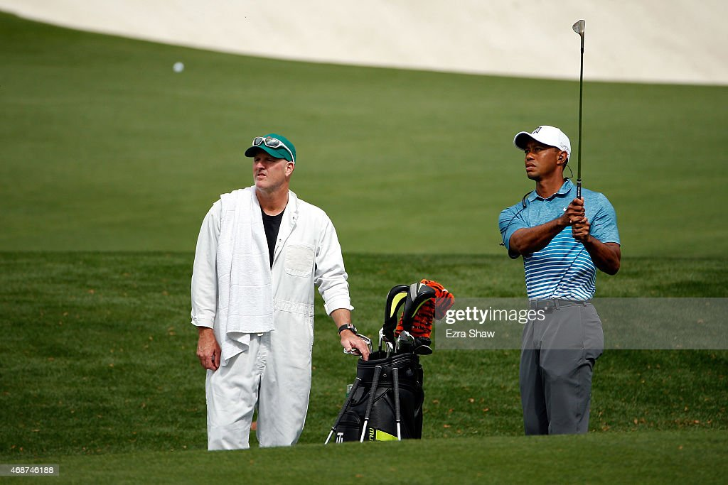 <a gi-track='captionPersonalityLinkClicked' href=/galleries/search?phrase=Tiger+Woods&family=editorial&specificpeople=157537 ng-click='$event.stopPropagation()'>Tiger Woods</a> (R) of the United States hits a chip shot on the practice range as caddie <a gi-track='captionPersonalityLinkClicked' href=/galleries/search?phrase=Joe+LaCava&family=editorial&specificpeople=695531 ng-click='$event.stopPropagation()'>Joe LaCava</a> (L) looks on during a practice round prior to the start of the 2015 Masters Tournament at Augusta National Golf Club on April 6, 2015 in Augusta, Georgia.