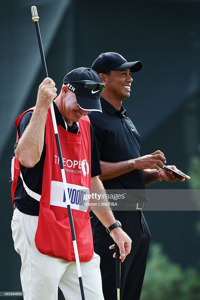 Tiger Woods (R) of the United States laughs with caddie Joe LaCava (L) on the sixth green during the second round of The 143rd Open Championship at Royal Liverpool on July 18, 2014 in Hoylake, England.