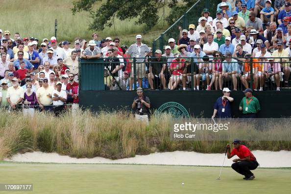 Tiger Woods of the United States lines up a putt on the fourth hole during the final round of the 113th US Open at Merion Golf Club on June 16 2013...