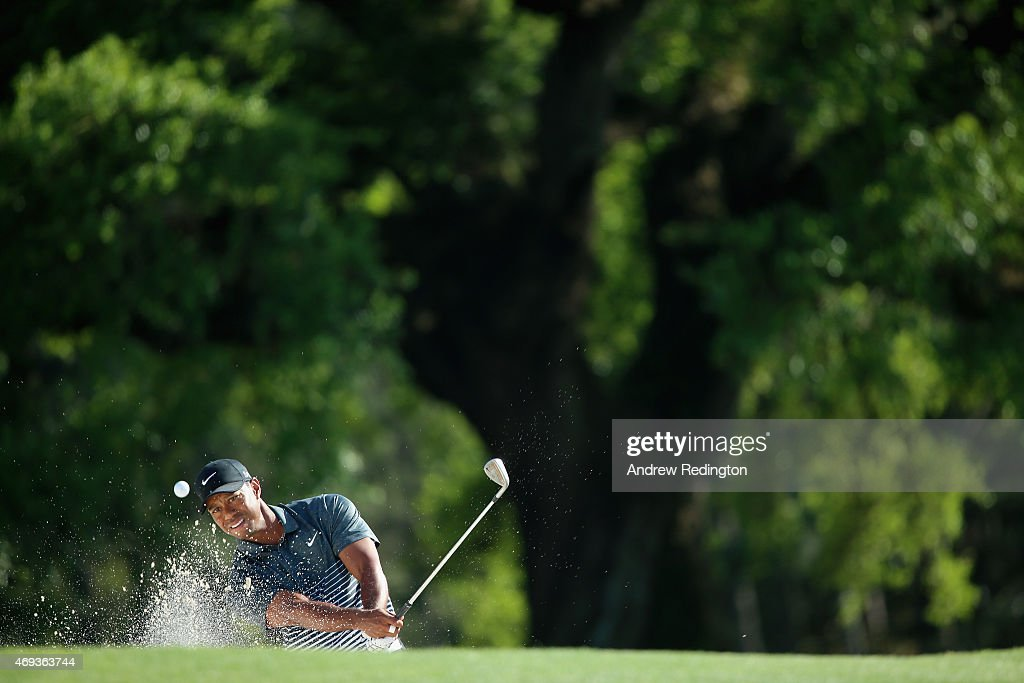Tiger Woods of the United States plays a bunker shot on the 18th hole during the third round of the 2015 Masters Tournament at Augusta National Golf...