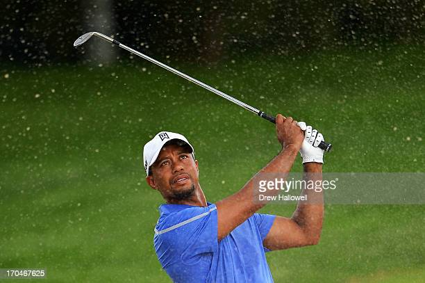 Tiger Woods of the United States plays his third shot from a bunker on the second hole during Round One of the 113th US Open at Merion Golf Club on...
