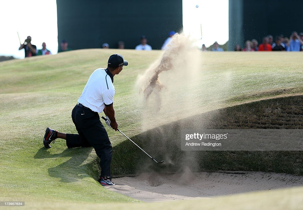 <a gi-track='captionPersonalityLinkClicked' href=/galleries/search?phrase=Tiger+Woods&family=editorial&specificpeople=157537 ng-click='$event.stopPropagation()'>Tiger Woods</a> of the United States plays out of a bunker on the 12th hole during the first round of the 142nd Open Championship at Muirfield on July 18, 2013 in Gullane, Scotland.