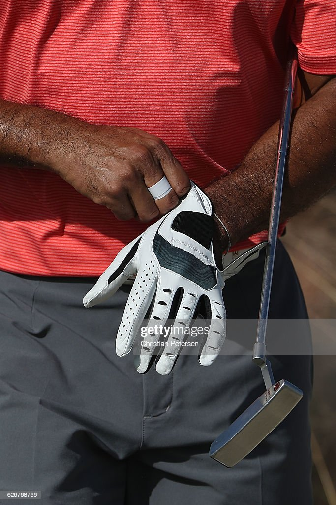 Tiger Woods of the United States puts on a glove during the pro-am ahead of the Hero World Challenge at Albany, The Bahamas on November 30, 2016 in Nassau, Bahamas.