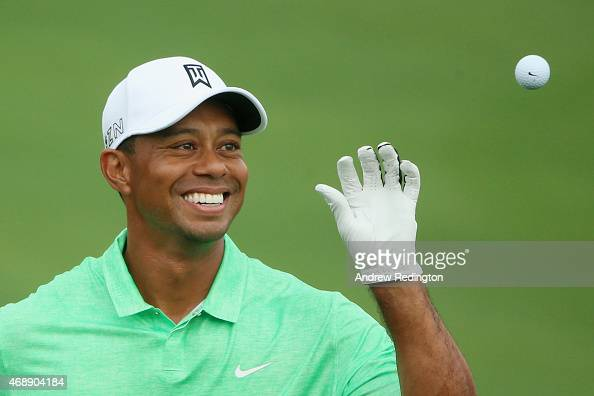 Tiger Woods of the United States reaches for a golf ball on the practice ground during a practice round prior to the start of the 2015 Masters...