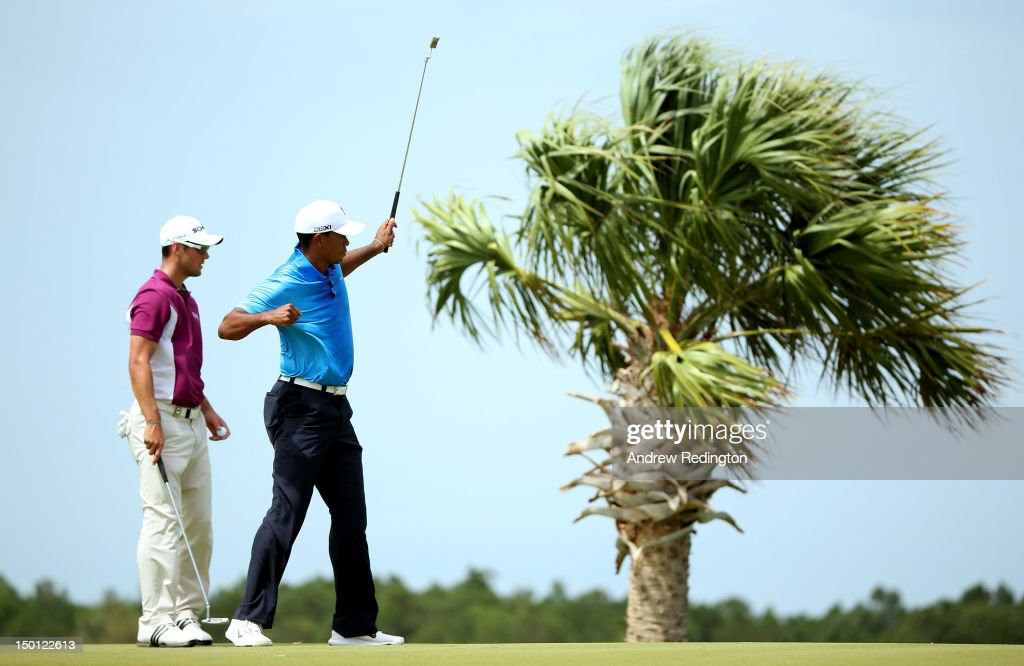 Tiger Woods of the United States (R) reacts after making a putt on the third hole as Martin Kaymer of Germany looks on during Round Two of the 94th PGA Championship at the Ocean Course on August 10, 2012 in Kiawah Island, South Carolina.