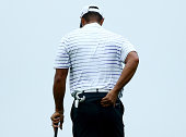 Tiger Woods of the United States rubs his back before hitting his second shot on the 17th hole during the second round of the 96th PGA Championship...