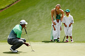 Tiger Woods of the United States waits a green as his girlfriend Lindsey Vonn son Charlie and daughter Sam look on during the Par 3 Contest prior to...