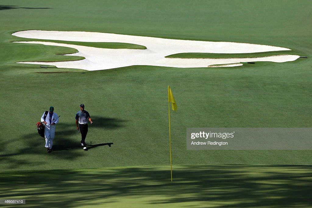 Tiger Woods of the United States walks to the tenth green with his caddie Joe LaCava during the third round of the 2015 Masters Tournament at Augusta National Golf Club on April 11, 2015 in Augusta, Georgia.