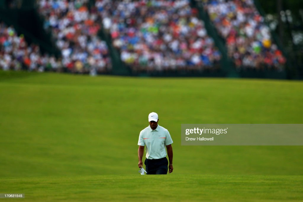 Tiger Woods of the United States walks up the 18th fairway during Round Three of the 113th US Open at Merion Golf Club on June 15 2013 in Ardmore...