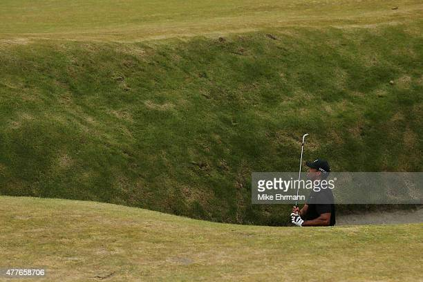 Tiger Woods of the United States watches his shot from a fairway bunker on the 18th hole during the first round of the 115th US Open Championship at...