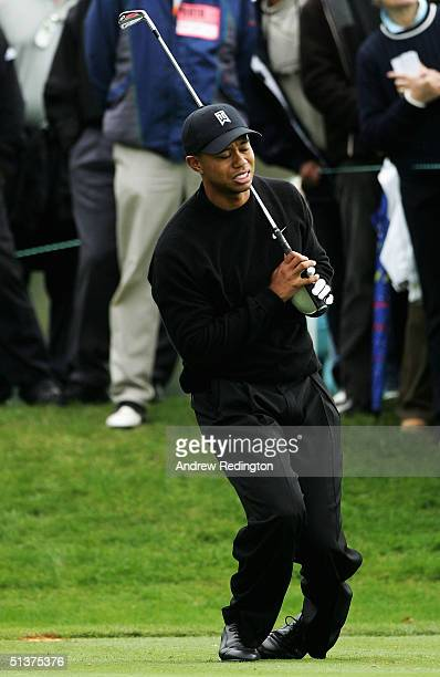 Tiger Woods of the United States winces in pain from a back injury on the sixth tee during the first round of the American Express Championship at...