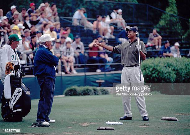 Tiger Woods of the United States with his coach Butch Harmon and caddie Mike 'Fluff' Cowan on the practice range the evening after the third round of...
