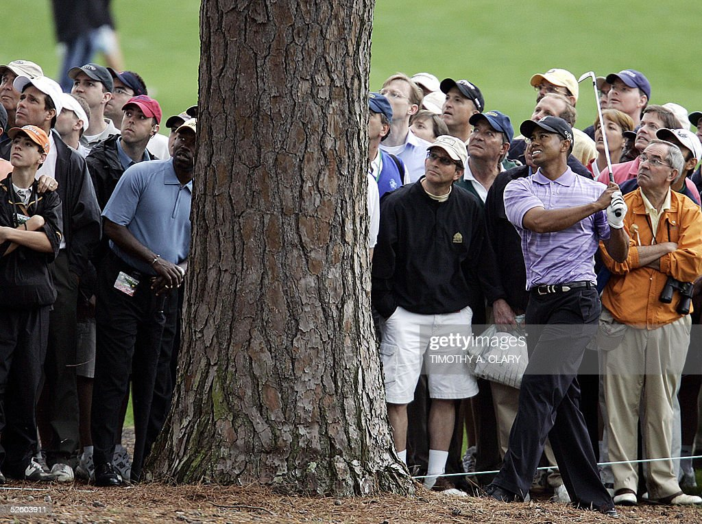 Tiger Woods of the US hits from behind a tree on the 8th fairway 08 April, 2005, during the 1st round of the 2005 Masters Golf Tournament at the Augusta National Golf Club in Augusta, Georgia. Woods finished the round at 2 over par, 74. AFP PHOTO/Timothy A. CLARY