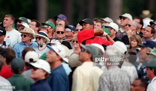 Tiger Woods of the US is surrounded by the gallery as he watches his tee shot on the 8th hole 13 April during the final round of the Masters...