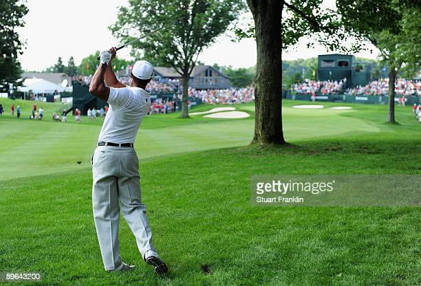 Tiger Woods of the US plays his approach shot on the 18th hole from behind a tree during the first round of the World Golf Championship Bridgestone...