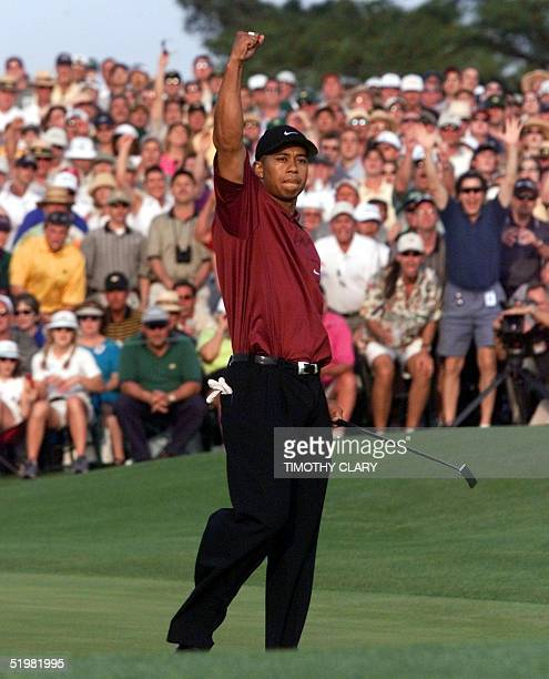 Tiger Woods of the US reacts to making the final winning putt on the 18th hole 08 April 2001 in the final round of the 2001 Masters Golf Tournament...