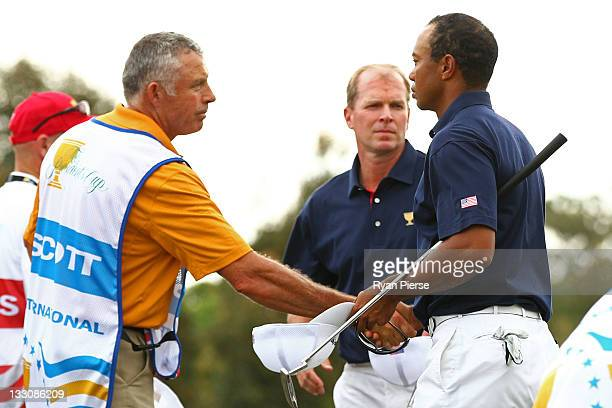 Tiger Woods of the US Team and Steve Williams caddie to Adam Scott shake hands as Steve Stricker of the US Team looks on after the completion of...