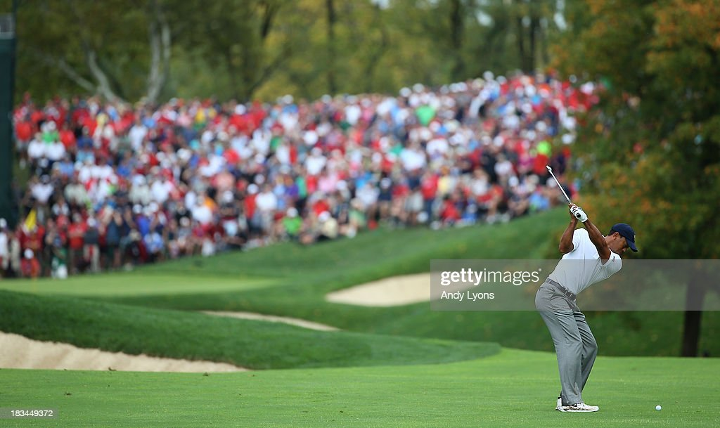 <a gi-track='captionPersonalityLinkClicked' href=/galleries/search?phrase=Tiger+Woods&family=editorial&specificpeople=157537 ng-click='$event.stopPropagation()'>Tiger Woods</a> of the U.S. Team hits his approach shot on the 17th hole during the Day Four Singles Matches at the Muirfield Village Golf Club on October 6, 2013 in Dublin, Ohio.