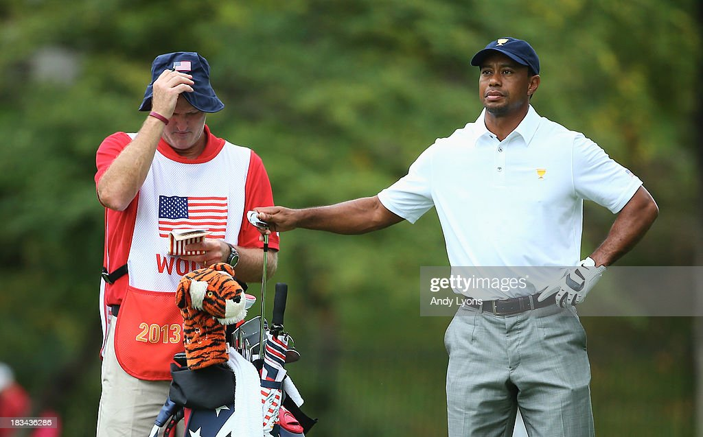 <a gi-track='captionPersonalityLinkClicked' href=/galleries/search?phrase=Tiger+Woods&family=editorial&specificpeople=157537 ng-click='$event.stopPropagation()'>Tiger Woods</a> of the U.S. Team pulls a club on the second hole as his caddie <a gi-track='captionPersonalityLinkClicked' href=/galleries/search?phrase=Joe+LaCava&family=editorial&specificpeople=695531 ng-click='$event.stopPropagation()'>Joe LaCava</a> looks during the Day Four Singles Matches at the Muirfield Village Golf Club on October 6, 2013 in Dublin, Ohio.