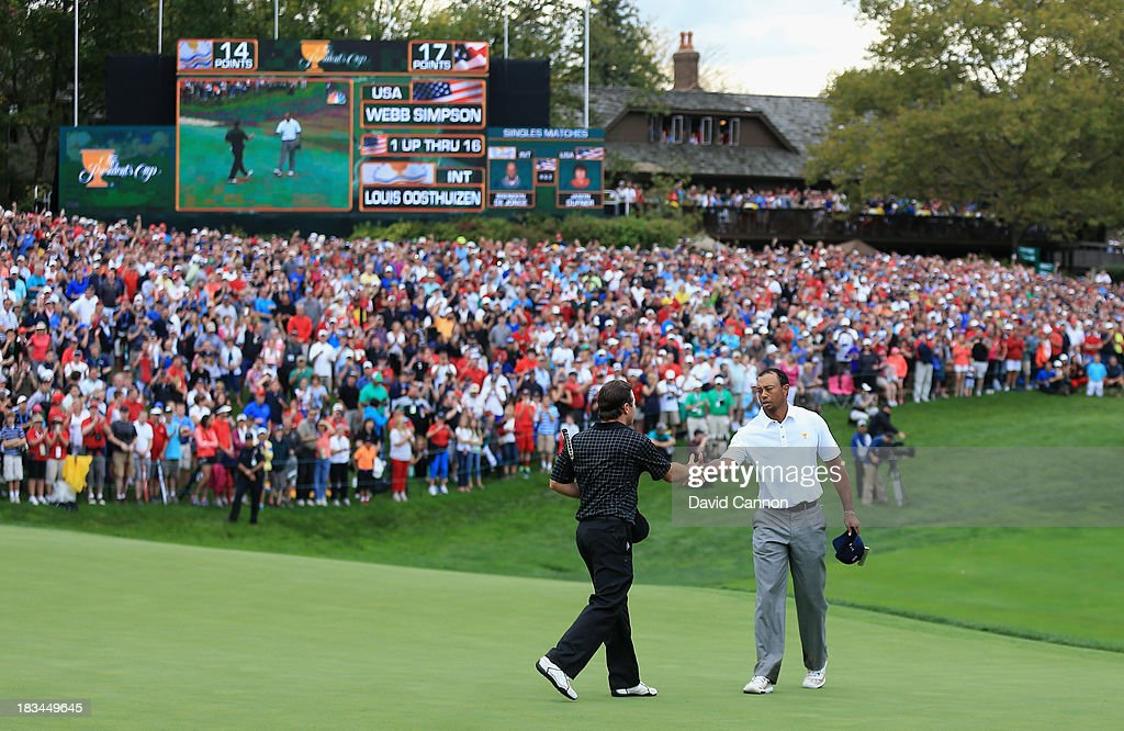Tiger Woods of the U.S. Team (R) shakes hands with Richard Sterne of South Africa and the International Team on the 18th green after Woods 1up victory won the Cup for the U.S.Team during the Day Four Singles Matches at the Muirfield Village Golf Club on October 6, 2013 in Dublin, Ohio.